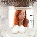Eggs in microwave Stock Photo