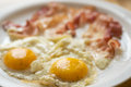 Eggs overeasy and bacon two fried on the plate Royalty Free Stock Images