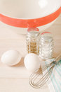 Eggs with salt and pepper shakers close up view looking down on two a wire whisk old fashioned a pink rimmed white bowl sits Royalty Free Stock Image