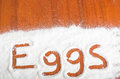 Eggs sign flour artwork with with food and handprints fun background with human handpints in scattered on a wooden tabletop Stock Photography