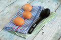 Eggs with spoon and dish towel on old wooden table Royalty Free Stock Image