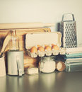 Eggs table ware grocery different stuff on kitchen table top toned image Royalty Free Stock Photography