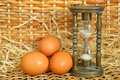 Eggs in village basket and hourglass as expectation concept Stock Photos