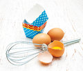 Eggs whisk and cupcake liners metal on a wooden background Stock Photography