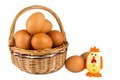 Eggs in a wicker basket with toy chicken isolated Stock Images