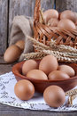 Eggs in wooden bowl with a little basket and linen sack background Royalty Free Stock Images