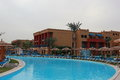 Egypt hotel with swimming pool blue water, sunbeds, palm trees