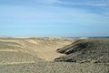 Egyptian desert and blue sky covered by black stones Royalty Free Stock Images