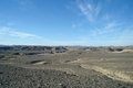 Egyptian desert and blue sky covered by black stones Royalty Free Stock Photos