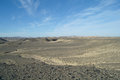 Egyptian desert and blue sky covered by black stones Stock Images