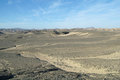 Egyptian desert and blue sky covered by black stones Royalty Free Stock Photography