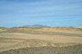 Egyptian desert and blue sky covered by black stones Royalty Free Stock Photo