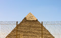 An egyptian pyramid behind a fence photograph of it depicts the troubled times in cairo Royalty Free Stock Photo