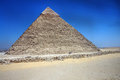 Egyptian pyramid with blue sky and sand Stock Photography
