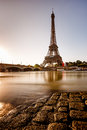 Eiffel tower and cobbled embankment of seine river at sunrise paris france Stock Photos