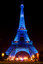 Eiffel Tower glowing blue illuminated at night in Paris, France Royalty Free Stock Photo