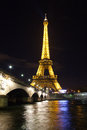 Eiffel tower over seine in paris night scene with lights on Stock Images