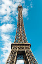 Eiffel Tower in Paris over cloudy blue sky