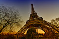 Title: The Eiffel Tower in winter. Bare trees faming Paris landmark