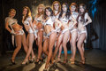 Eight beautiful showgirls posing on stage focus the girl in the center Stock Photo