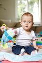 Eight months old baby boy sitting playing toy Royalty Free Stock Photography