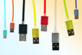 Eight multicolored usb cables hang vertically, on a gradient, tinted background. The family unites. future technologies.