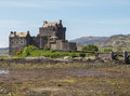 Eilean donan castle scotland view of the medieval in the scottish highlands at low tide stone bridge with scottish flag flying Royalty Free Stock Images