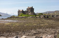 Eilean donan castle scotland view of in the scottish highlands loch duich in the distance as the tide is out with rocky shore and Royalty Free Stock Images