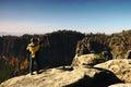El hombre está tomando las fotos por smartphone en pico en parque de los imperios de la roca y las está vigilando el valle Imágenes de archivo libres de regalías