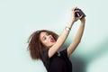 El inconformista hermoso de la chica joven toma las fotos tira el selfe tomando imágenes de sí mismo en cámara en vaqueros y Fotos de archivo