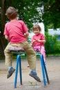 El muchacho y la muchacha en un oscilación en parque Foto de archivo libre de regalías