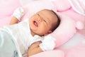 El niño recién nacido de la cara mintió en cama rosada Imagen de archivo