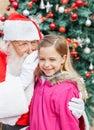 El oído de santa claus whispering in cute girl Fotografía de archivo libre de regalías