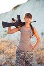 El soldado de sexo femenino joven se vistió en un camuflaje con un arma en el o Fotografía de archivo libre de regalías