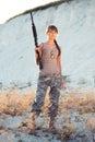 El soldado de sexo femenino joven se vistió en un camuflaje con un arma en el o Imagenes de archivo