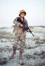 El soldado de sexo femenino joven se vistió en un camuflaje con un arma en el o Foto de archivo libre de regalías