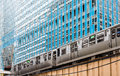 El train in chicago under blue glass tower commuter downtown on elevated tracks a office Royalty Free Stock Photography