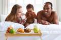 Elated family having breakfast sitting on bed at home cheerful american Royalty Free Stock Photography