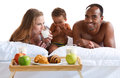 Elated family having breakfast sitting on bed at home concept of cheerful american Royalty Free Stock Images