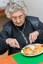Eldelry woman eating her lunch at home Royalty Free Stock Photography