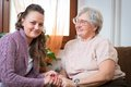 Eldelry woman women with her home caregiver Stock Image