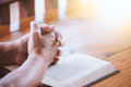 Elder woman hands folded in prayer on a Holy Bible Royalty Free Stock Photo