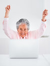 Elder woman with a laptop happy and arms up Royalty Free Stock Photo