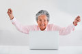 Elder woman online success celebrating her with arms up Stock Image