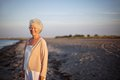 Elder woman portrait of relaxed elderly standing at the beach happy old lady standing alone on the beach with lots of copyspace Stock Image