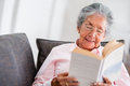 Elder woman reading a book at home and smiling Royalty Free Stock Photo