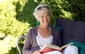 Elder woman reading a book sitting on chair in backyard garden holding and looking at camera smiling Royalty Free Stock Image