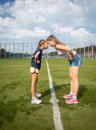Elder and younger sister standing head to head on grass conceptual outdoor shot of Royalty Free Stock Image