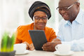 Elderly african couple tablet lovely using computer at home Stock Images