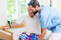 Elderly care nurse helping senior from wheel chair to bed Royalty Free Stock Photo